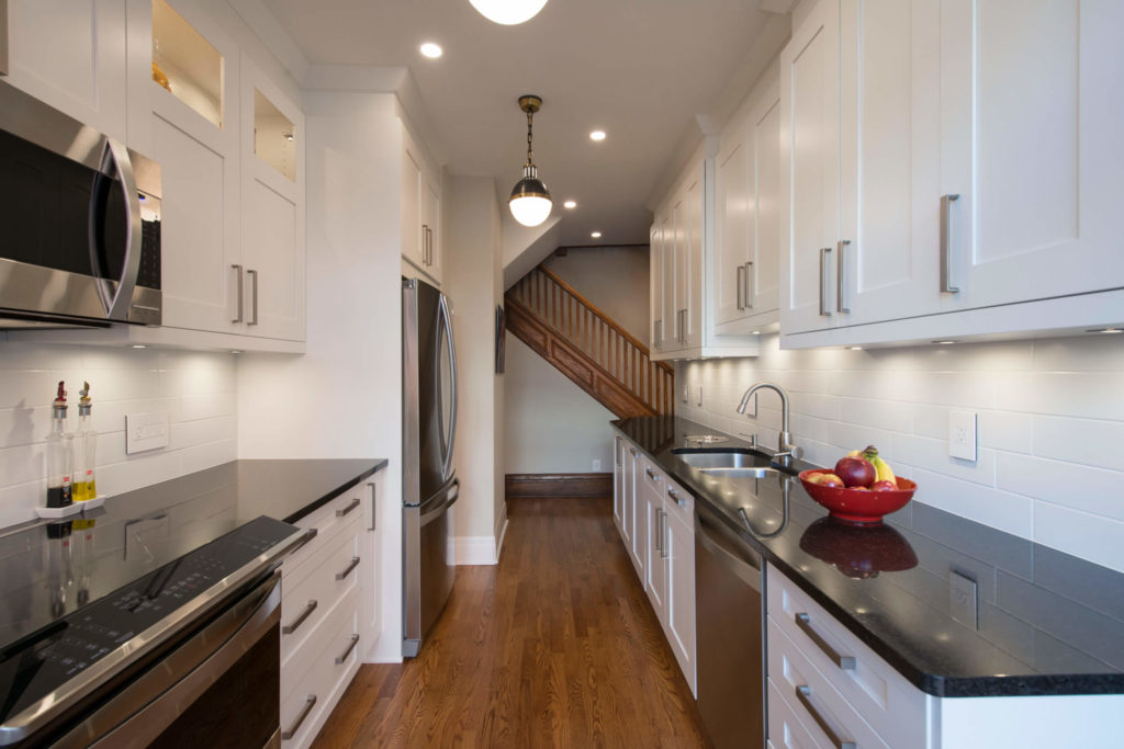 Side-by-side galley-style contemporary kitchen with shaker-style cabinets and crown molding.