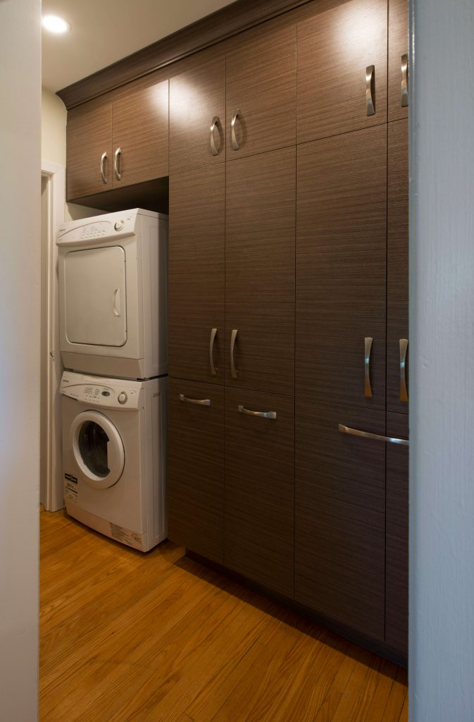 Custom cabinetry around a washer-dryer stack.