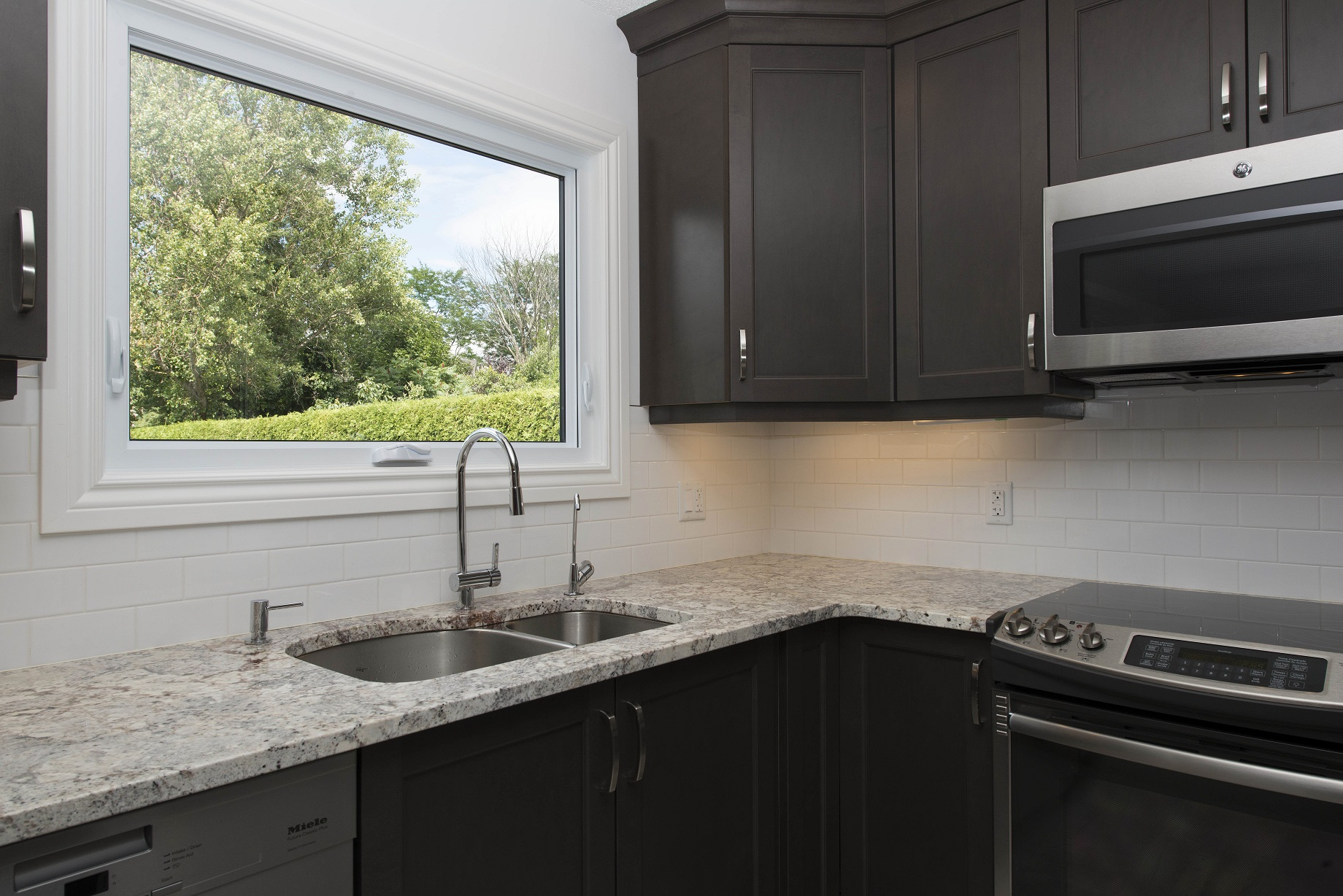 A Modern Kitchen Sink With Window Looking Out Onto Green Yard All To