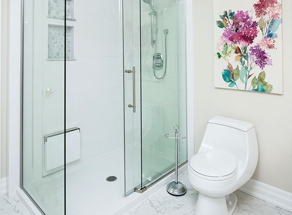 A luxurious bathroom enclosure is visible next to a modern toilet design with a beautiful piece of art above it.
