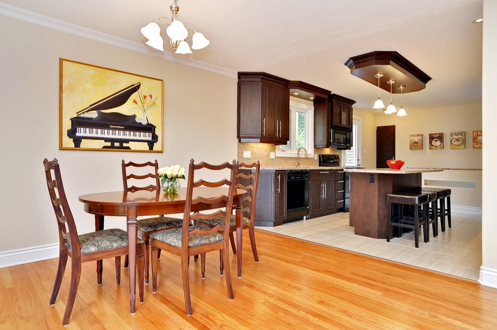 A three-quarters view of a renovated kitchen and dining room, with beautiful hardwood floors.