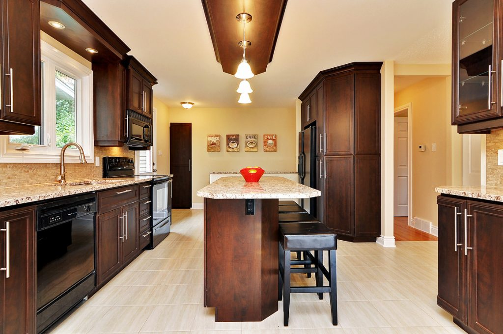 A side of view of an open kitchen reno with an island and seating.
