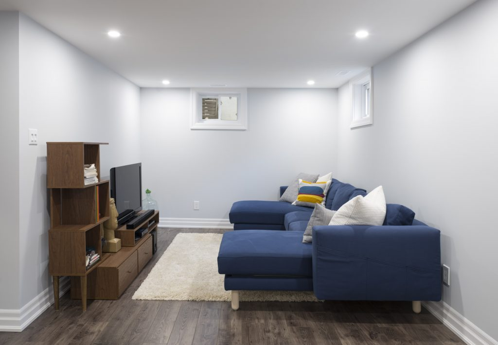 A cozy home theatre space, with a modest TV and comfortable couch, are a welcome addition to this basement renovation.
