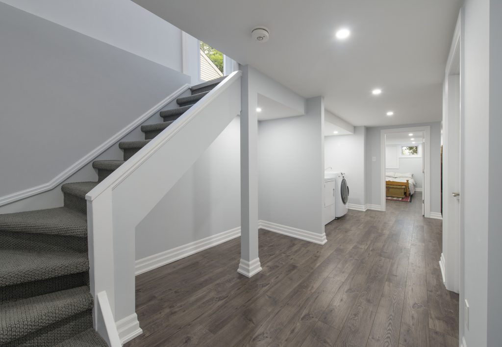 A view beneath a finished basement staircase, showcasing plenty of storage space.