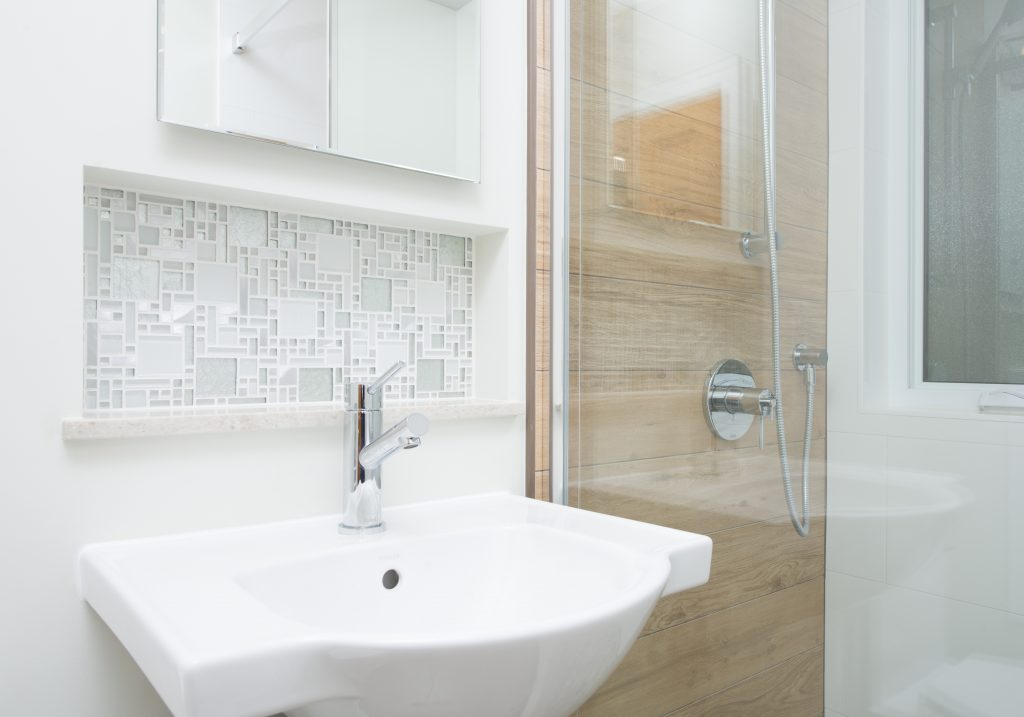 A beautiful view of an inset shelf behind a sink, next to a glass-enclosed shower with beautiful tile features.