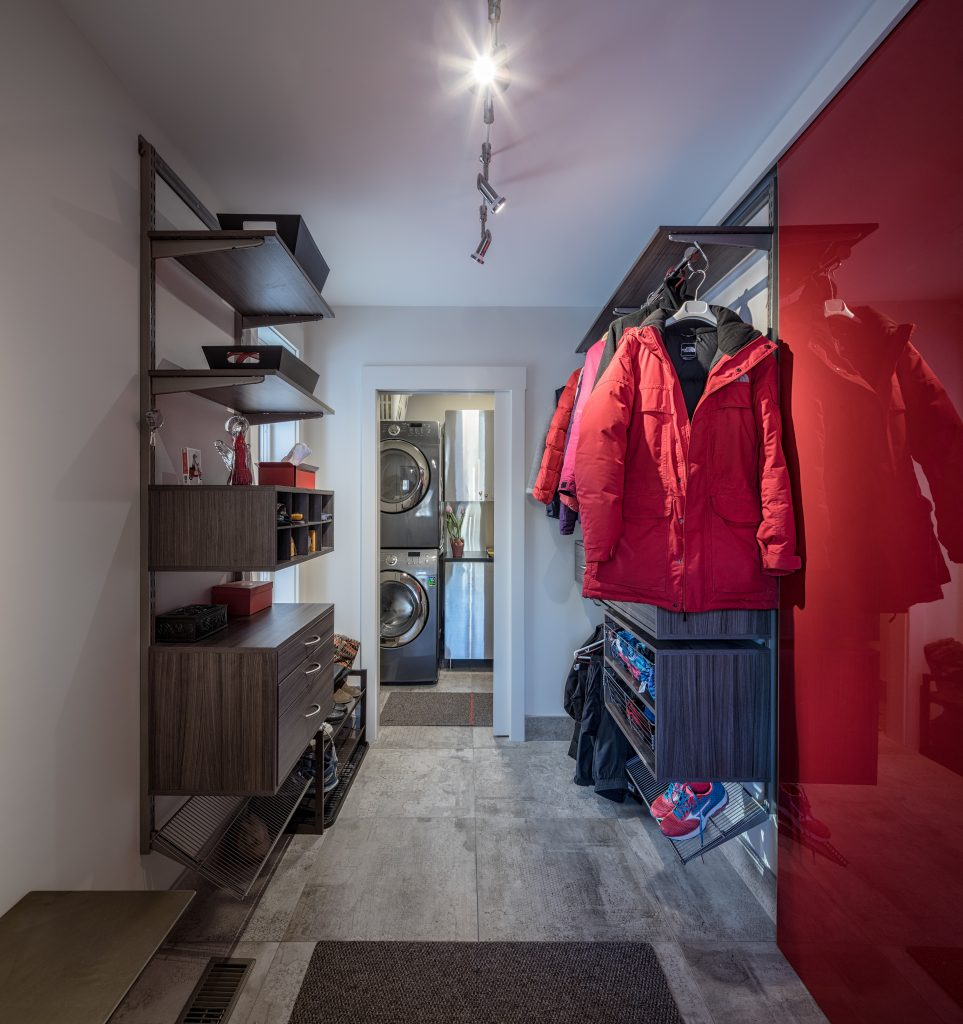 A modern, stylish mudroom with red a red wall and a red jacket hanging up offers a look into the home beyond.