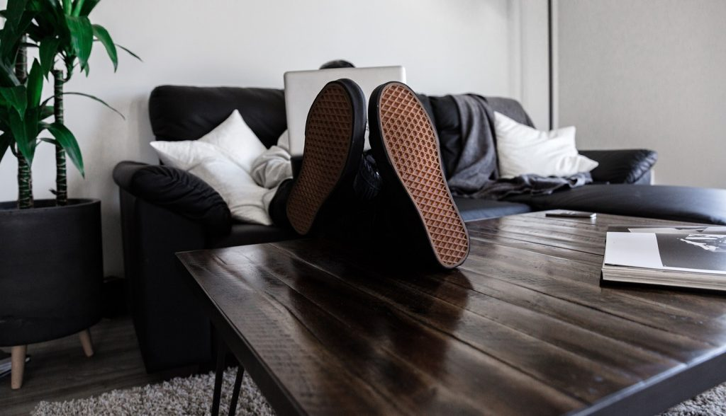Someone sitting at a low couch props their feet up on a coffee table, resting a laptop on their legs.