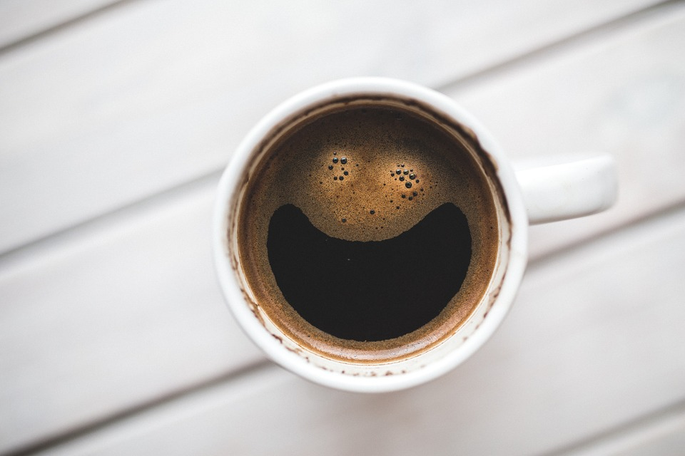 "A fresh cup of coffee ""smiles"" due to the foam and bubbles on its surface."