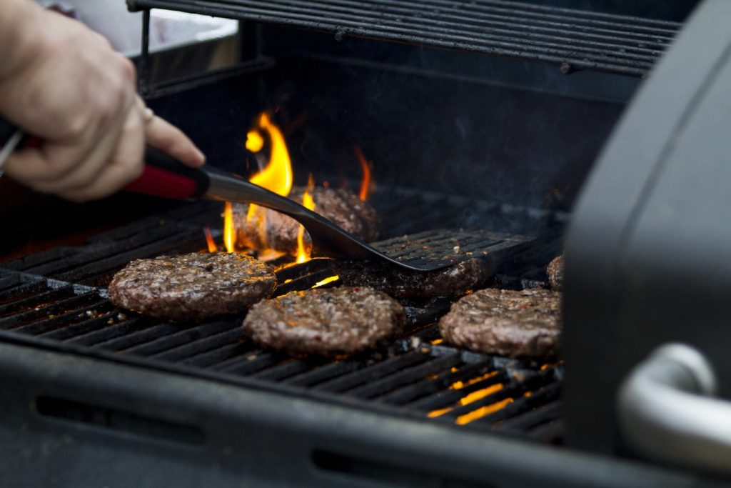 A person flips burgers on a barbecue grill.