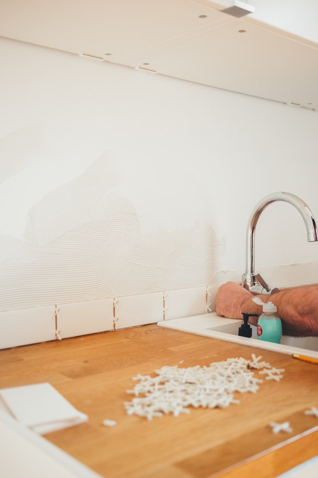A contractor sets kitchen tile behind a sink and countertop to create a backsplash.