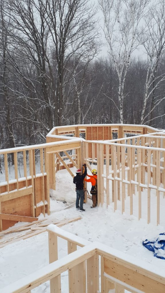 The Sunter Homes team of custom home builders work in fresh snow to finish some framing for a new build.