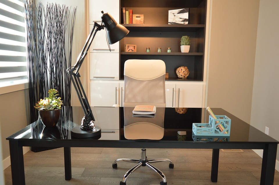 A simple, modern desk set up with a lamp sits in front of a large shelving unit with built-in cupboards and drawers.