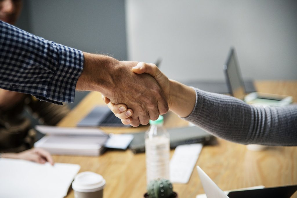 Two people shake hands across a table during a meeting.