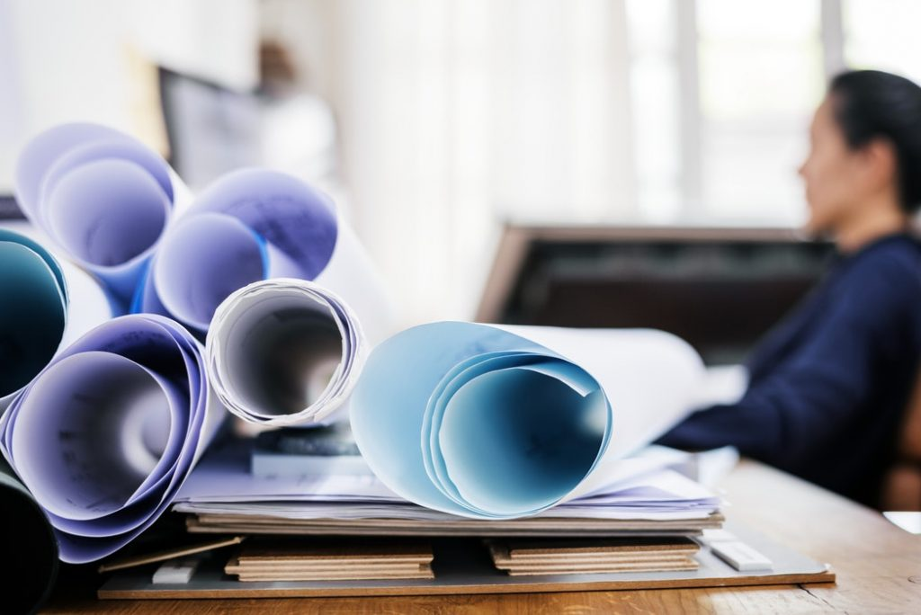 A person sits at a desk with a stack of blueprints rolled up on their desk.