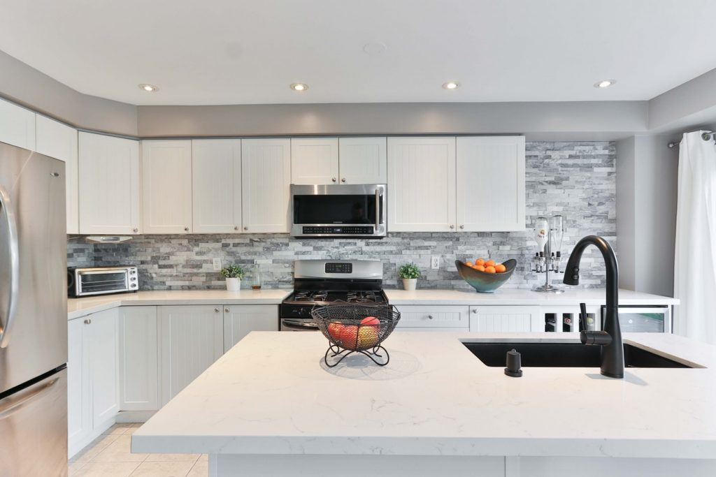A contemporary kitchen design that incorporates the microwave into the range hood above the stove.