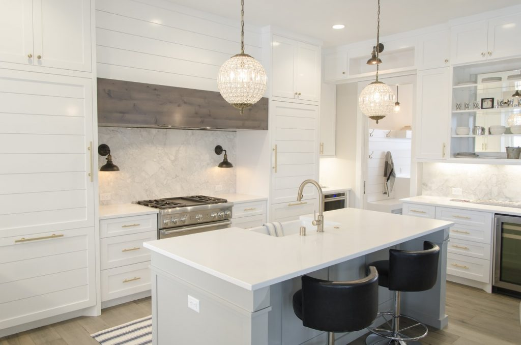 A stylish, white-and-gold modern kitchen with an island and bar seating.