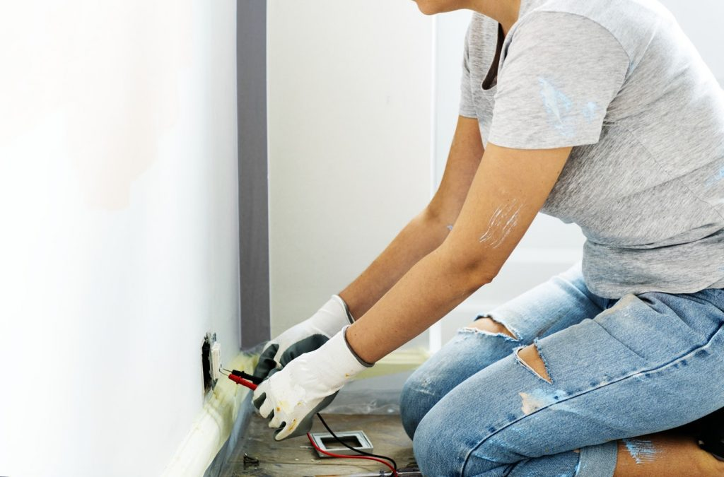 A woman kneels by an outlet to test electrical wiring.