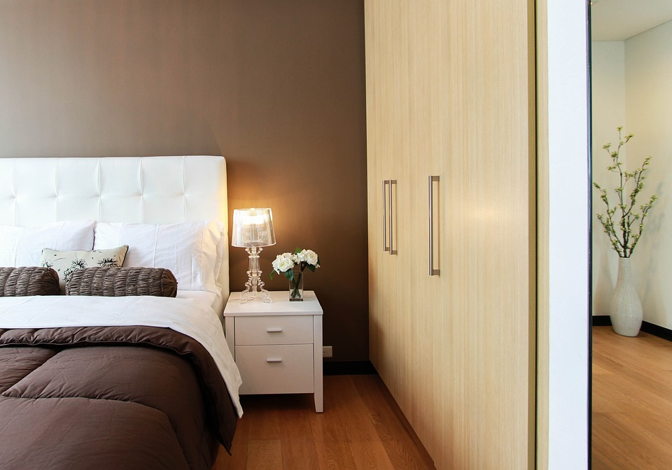 A large closet and mirror face onto a bed in a modern bedroom.