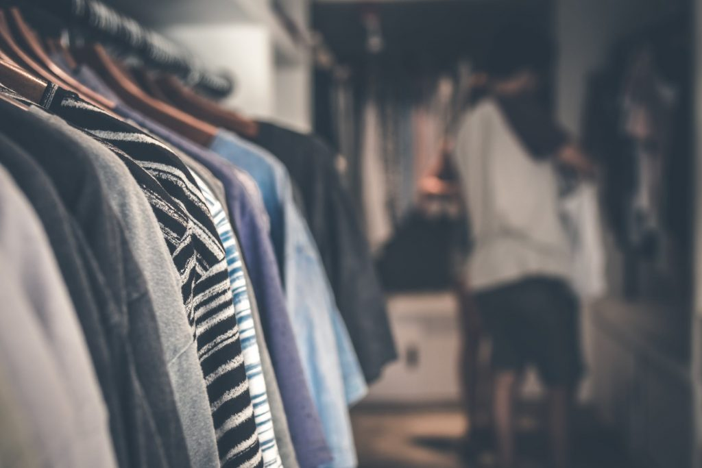 Shirts hang on the rack in a walk-in closet as a man looks for clothes in front of a mirror.
