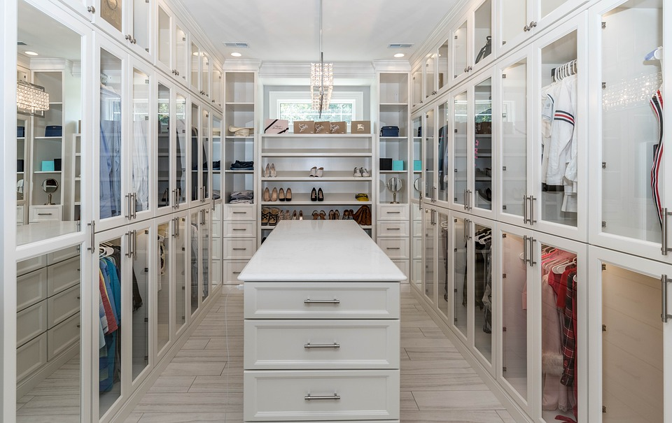 A beautiful walk-in closet with central island and glass doors for all items.