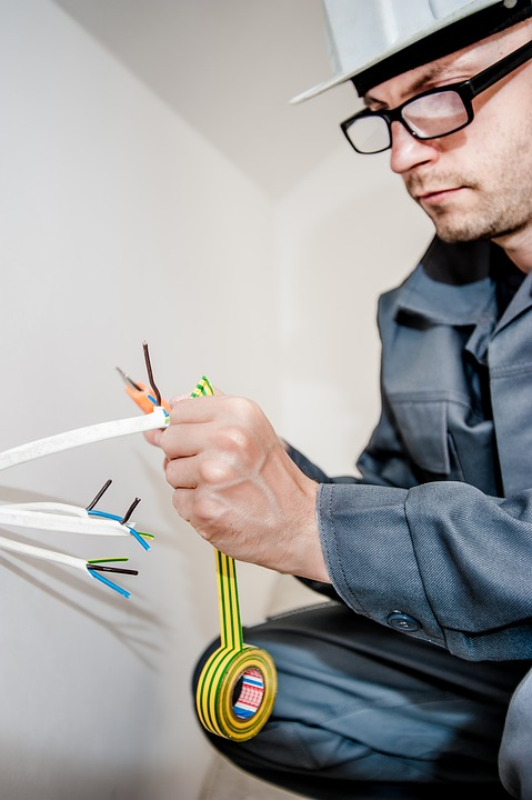 An electrician working on wiring in a home.