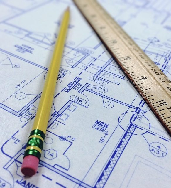 A pencil and ruler sit on top of a set of blueprints.