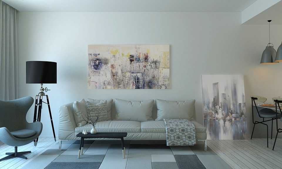 A contemporary living room with a modern couch and chair, as well as abstract paintings.