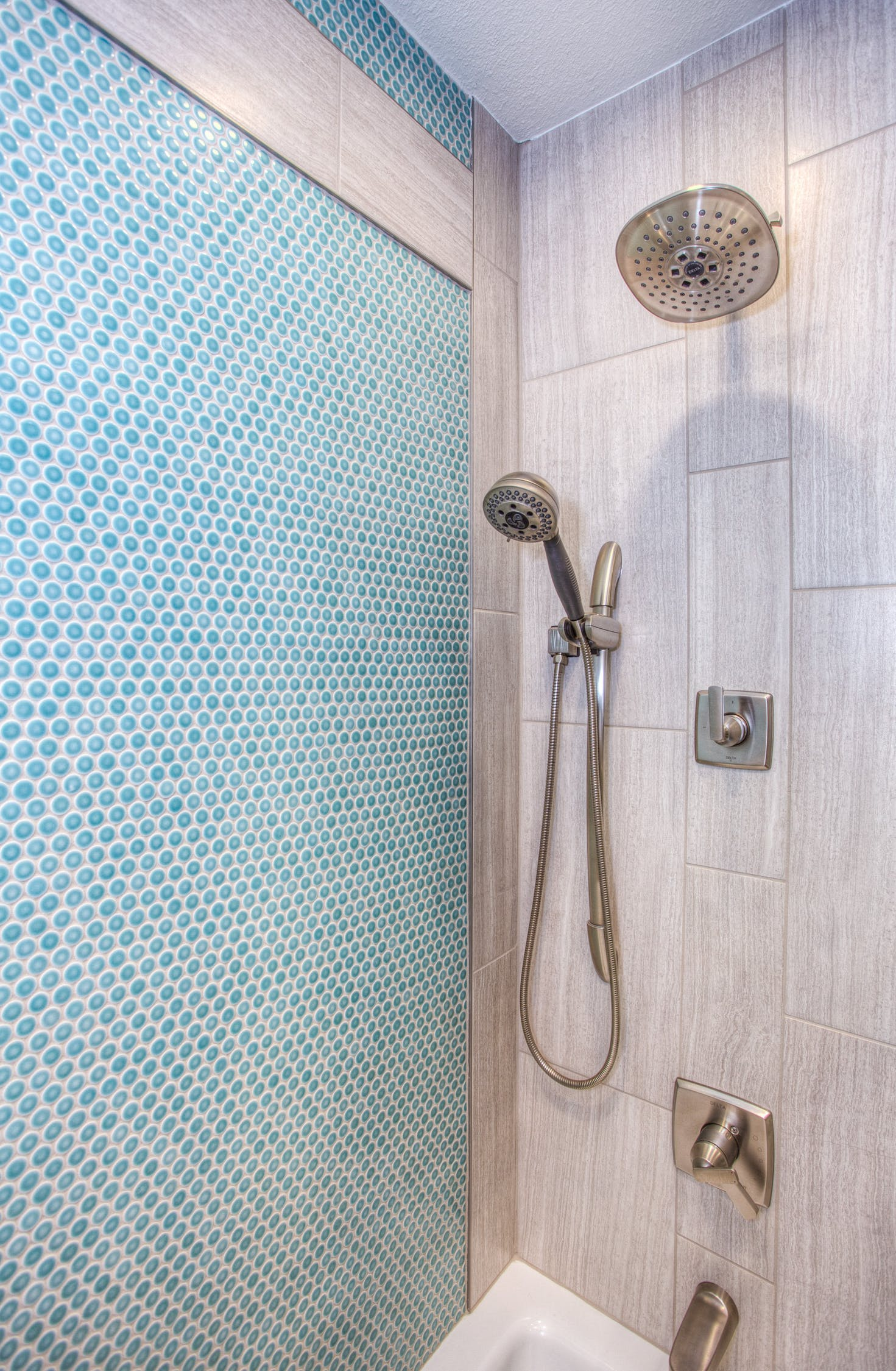 renovated shower with large and small tiles